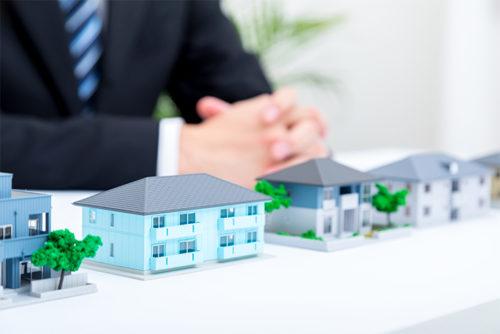 小さな家の模型を4つ並べた机に座っているスーツを着た男性の手元